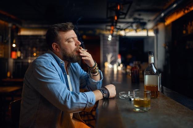 Zestresowany brodaty mężczyzna pije alkohol przy kasie w barze. jeden mężczyzna odpoczywający w pubie, ludzkie emocje i zajęcia rekreacyjne, depresja, łagodzenie stresu