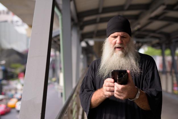 Zestresowany dojrzały brodaty mężczyzna przy użyciu telefonu i patrząc zszokowany na kładkę w mieście