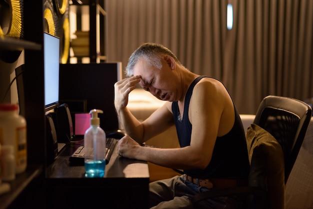 Zestresowany dojrzały japończyk ma ból głowy podczas pracy z domu