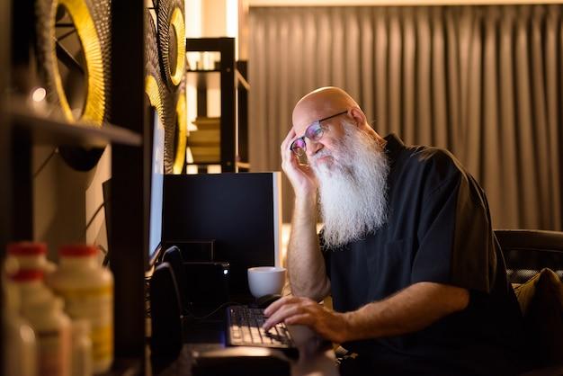 Zestresowany dojrzały łysy brodaty mężczyzna wyglądający na zmęczonego podczas pracy w godzinach nadliczbowych w domu późno w nocy