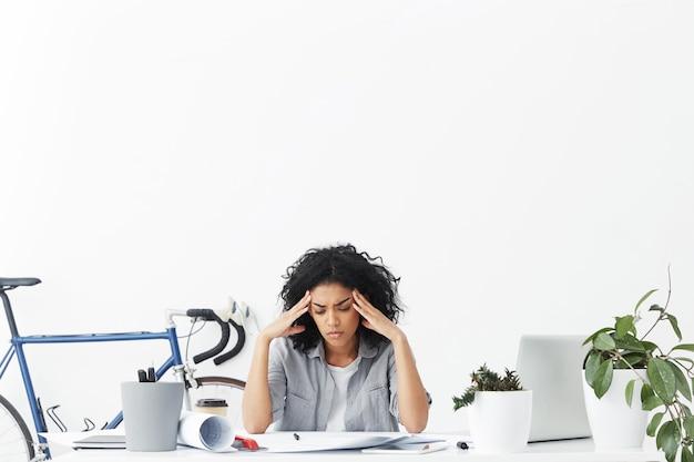 Zestresowany i nieszczęśliwy inżynier-student z afryki ściskający jej skronie