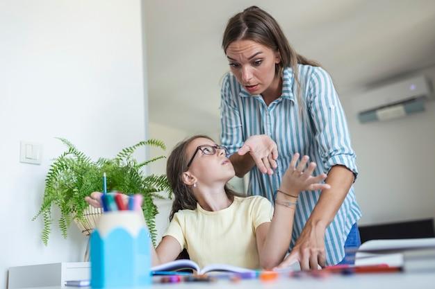 Zestresowany matka i syn sfrustrowani niepowodzeniem odrabiania lekcji, koncepcja problemów szkolnych. smutna dziewczynka odwrócona od mamy, nie chce odrabiać nudnej pracy domowej