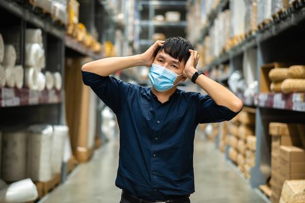 Zestresowany menadżer z maską medyczną w hurtowni podczas pandemii koronawirusa