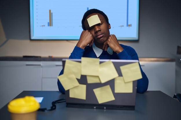 Zestresowany menedżer pracuje na laptopie, nocny styl życia w biurze. mężczyzna przy stole, ciemne wnętrze centrum biznesowego, nowoczesne miejsce pracy