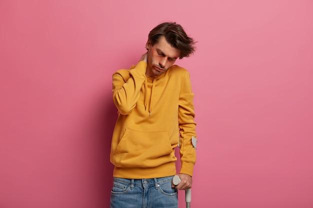 Zestresowany mężczyzna ma problemy z kręgosłupem po upadku z wysokości, dotyka szyi i chodzi o kulę, myśli o ubezpieczeniu zdrowotnym, ma długi, męczący okres rekonwalescencji. pojęcie opieki zdrowotnej