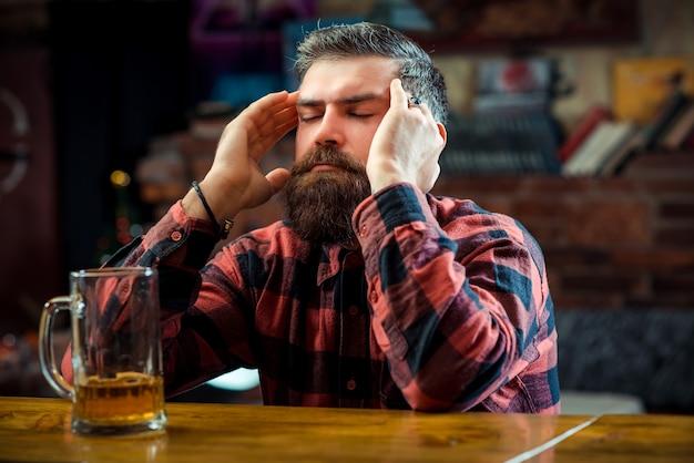 Zestresowany mężczyzna pije piwo w pubie. samotny brodaty mężczyzna siedzący przy barze.