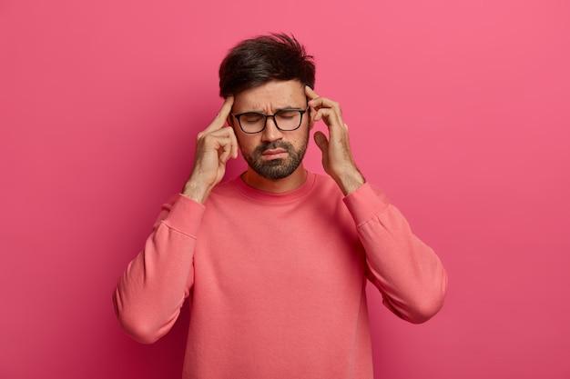 Zestresowany mężczyzna pociera skronie, ma bóle głowy, zamyka oczy, aby złagodzić ból
