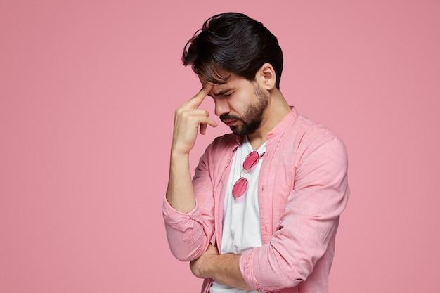 Zestresowany mężczyzna ubrany o ból głowy na białym tle nad różową ścianą