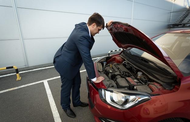 Zestresowany młody biznesmen patrząc pod maskę samochodu