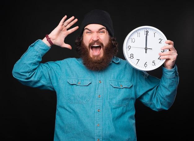 Zestresowany, młody, brodaty mężczyzna trzyma duży biały zegar i bardzo zestresowany patrzy w kamerę w pobliżu czarnej ściany