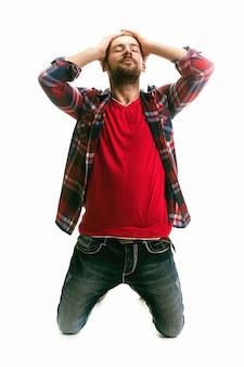 Zestresowany młody chłopak na kolanach z rękami we włosach, przygnębiony mężczyzna