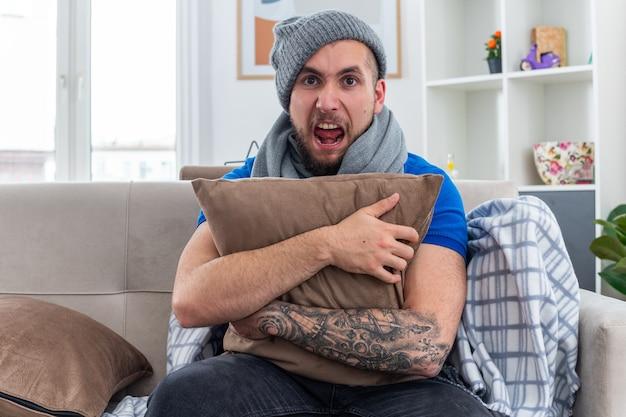 Zestresowany młody chory mężczyzna ubrany w szalik i czapkę zimową, siedzący na kanapie w salonie, przytulający poduszkę krzycząc