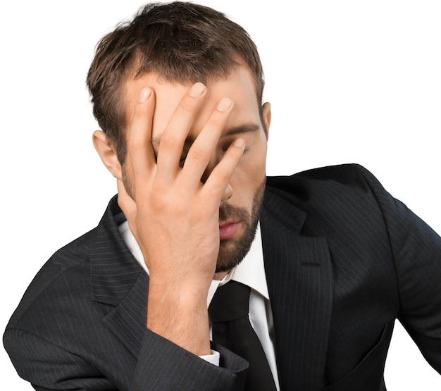 Zestresowany młody człowiek, ręka na głowie na białym tle