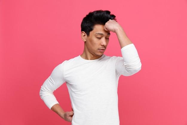 Zestresowany młody człowiek trzymając rękę na talii i na czole z zamkniętymi oczami