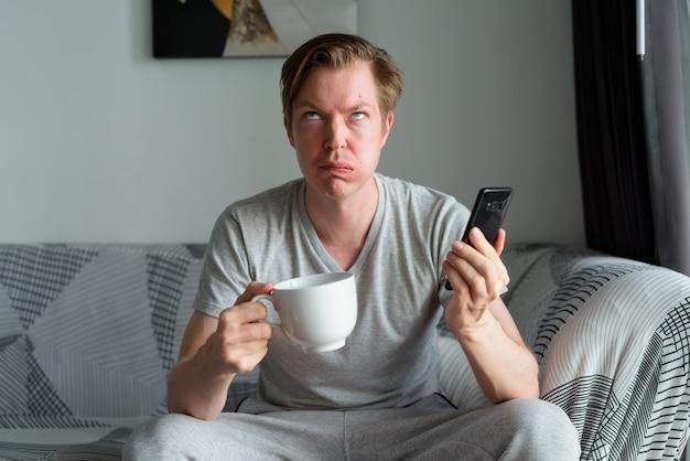 Zestresowany młody człowiek z kawą wygląda na zirytowanego podczas korzystania z telefonu w domu