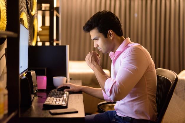 Zestresowany młody indyjski biznesmen kaszle podczas pracy w domu w godzinach nadliczbowych późno w nocy