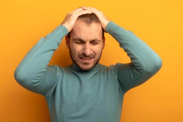 Zestresowany młody kaukaski mężczyzna kładzie ręce na głowie z zamkniętymi oczami na białym tle na pomarańczowej ścianie