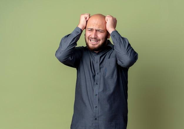 Zestresowany młody łysy mężczyzna call center kładzie ręce na głowie z zamkniętymi oczami na białym tle na oliwkowej ścianie