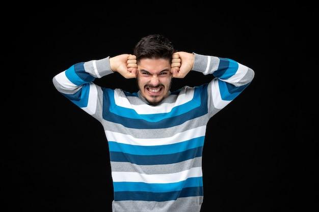 Zestresowany młody mężczyzna w niebieskiej koszulce w paski z rękami na głowie