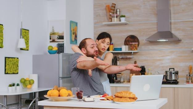 Zestresowany przedsiębiorca pracuje na laptopie, siedząc na stole w kuchni, podczas gdy jego żona gotuje śniadanie. nieszczęśliwy, zestresowany, sfrustrowany, wściekły negatywny i zdenerwowany freelancer w piżamie krzyczy rano