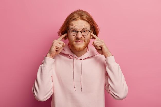 Zestresowany rudowłosy mężczyzna przeszkadza głośno sąsiadowi