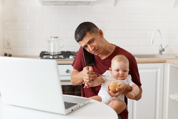 Zestresowany smutny mężczyzna brunetka ubrany w bordową koszulkę w stylu casual, siedzący przy stole w kuchni, rozmawiający przez smartfona, mający smutek, karmiący swoją córeczkę puree owocowym.