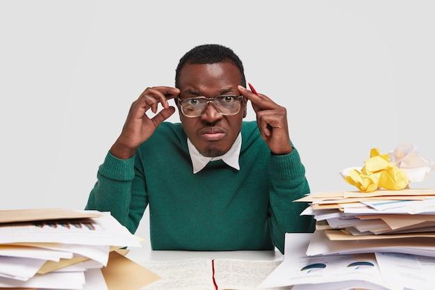 Zestresowany szef ma ból głowy, niezadowolony wyraz twarzy, musi płacić faktury, ma dużo rachunków, studiuje księgowość w miejscu pracy