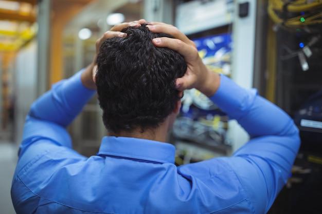Zestresowany technik pracujący nad konserwacją serwera