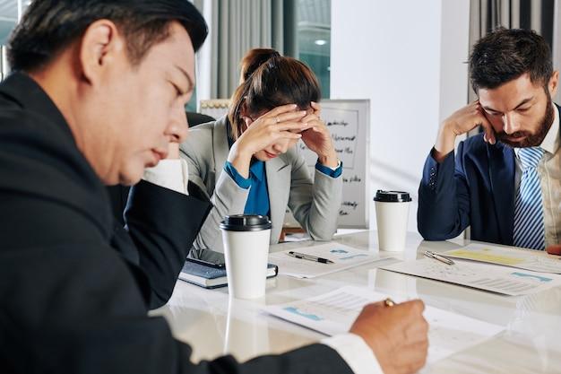 Zestresowany zespół biznesowy zebrał się, aby omówić inwestycje i sposoby ożywienia gospodarki po kryzysie epidemicznym