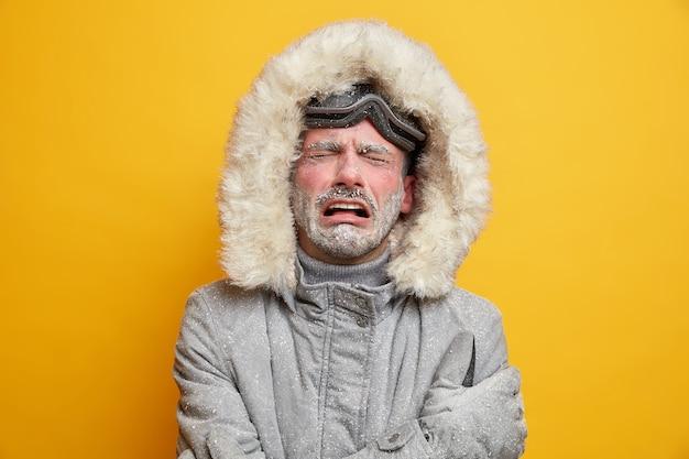 Zestresowany, zimny mężczyzna płacze z rozpaczy ma niezadowolony wyraz twarzy zastygłą twarz pokrytą szronem nosi szarą kurtkę.