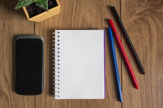 Zeszyt do pisania leży na stole. narzędzia biurowe. zestaw długopisów, telefonu, papieru i kwiatów. miejsce na nagranie.