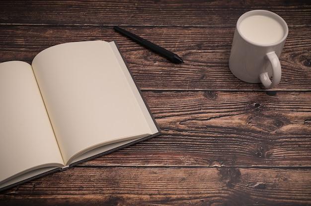 Zeszyt i szklanka mleka leżą na biurku.