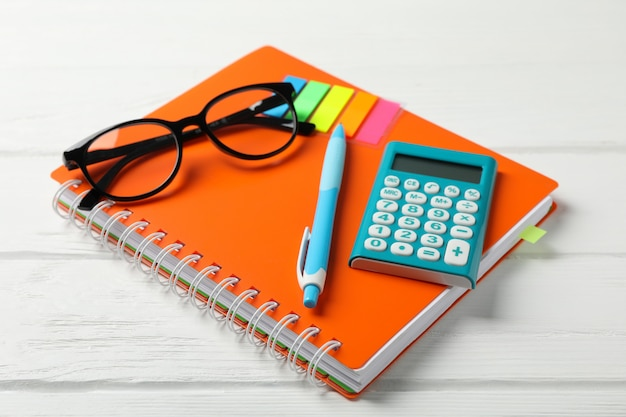 Zeszyt, okulary, kalkulator, długopis i naklejki na drewnianym stole, z bliska
