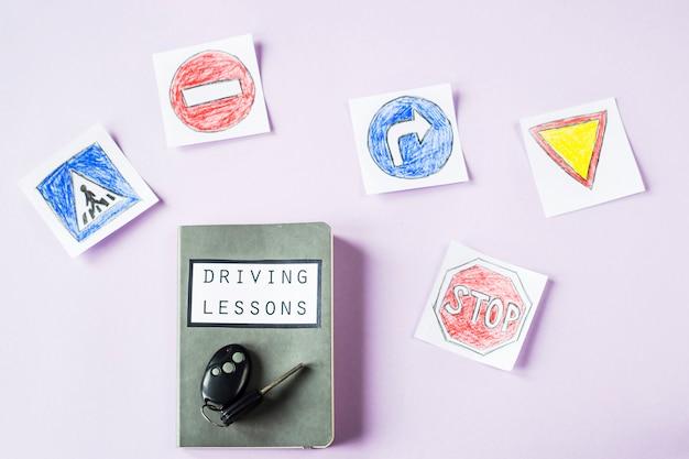 Zeszyt szkoleniowy na lekcje jazdy i zasady ruchu drogowego obok rysunków na znak drogowy, aby uzyskać prawo jazdy