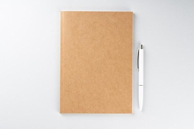 Zeszyt szkolny i długopis na szarym tle, spiralny notatnik na stole
