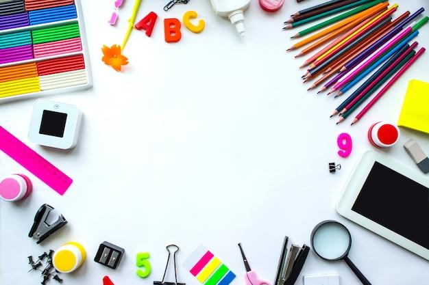 Zeszyt szkolny i różne artykuły papiernicze z miejscem na kopię. szkoła dostarcza artykuły papiernicze, kredki, farby, papier na żółtym tle, powrót do koncepcji szkoły, nowoczesna edukacja podstawowa. układ płaski.