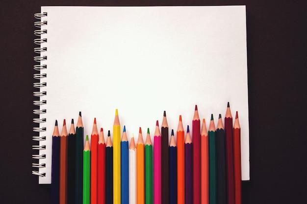 Zeszyt szkolny, kolorowe kredki rainbow poruszają się obok siebie. akcesoria szkolne