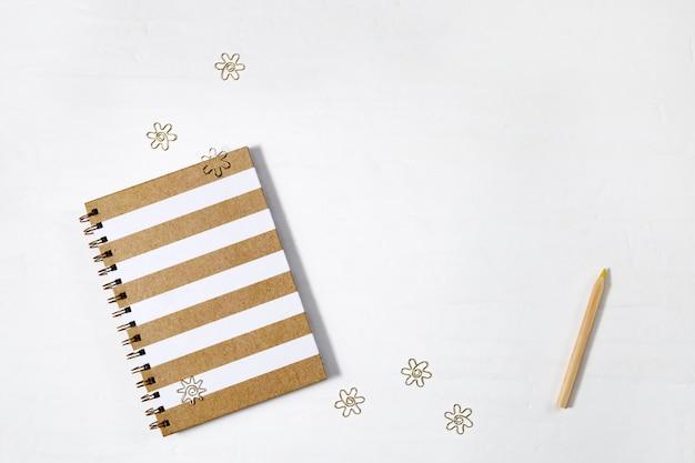 Zeszyt szkolny na wiosnę, drewniany ołówek i złote klipsy z metalowymi elementami na białej przestrzeni roboczej. powrót do koncepcji szkoły. widok z góry.