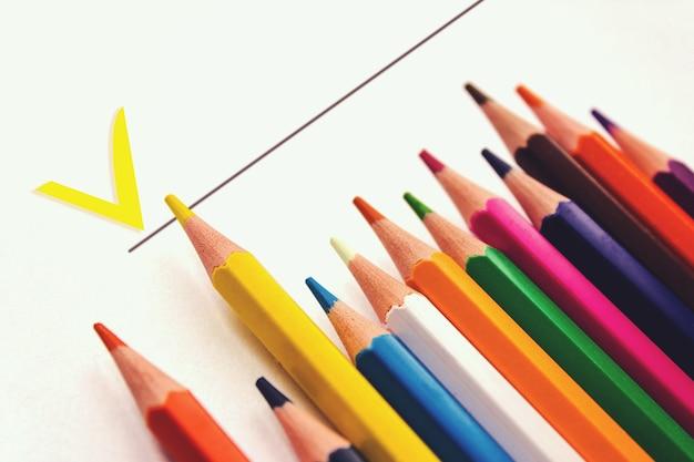 Zeszyt szkolny, rząd różnych kolorowych ołówków. akcesoria szkolne, powrót do koncepcji szkoły, nowoczesna edukacja podstawowa. mieszkanie leżało