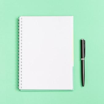 Zeszyt z czystą stroną i czarnym długopisem