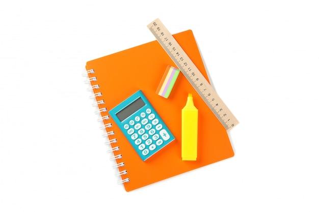 Zeszyt z kalkulatorem, markerem, gumką i linijką na białym tle