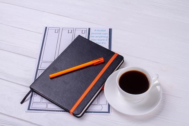 Zeszyt z piórem i filiżanką kawy.