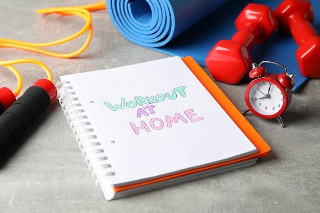 Zeszyt z treningiem w domu i sprzętem fitness na szarej powierzchni