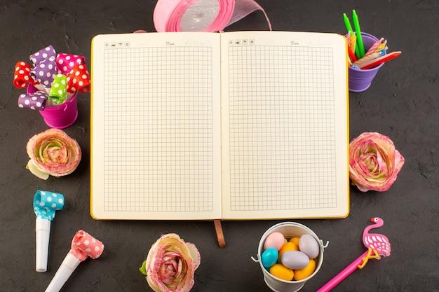 Zeszyt z widokiem z góry i cukierki z kwiatami, świecami i ołówkami na ciemnym biurku, kompozycja fotograficzna cukierków