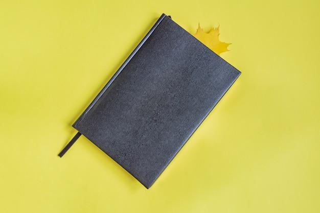 Zeszyt ze sztucznej skóry w czarnym kolorze z liściem klonu jako żółta zakładka.