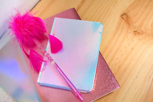 Zeszyty i książki w opalizujących i jasnych kolorach z brokatem i bardzo pięknym i kobiecym różowym piórkiem.