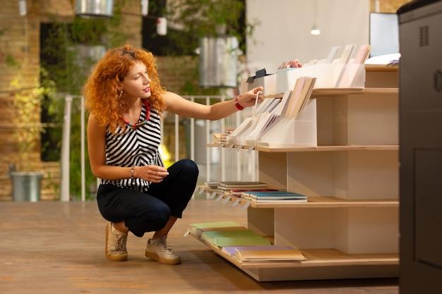 Zeszyty na półkach. kręcona rudowłosa pracownica sklepu papierniczego układająca zeszyty na półkach