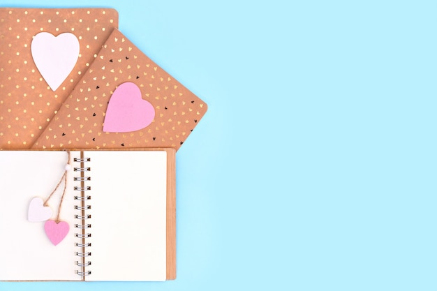 Zeszyty z różowymi i białymi drewnianymi sercami. wyślij wiadomość do swojego kochanka w walentynki.
