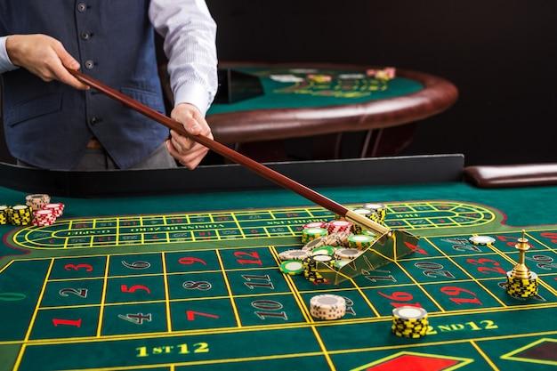 Żetony do gry na zielonym stole w kasynie. krupier zbiera żetony za pomocą kija