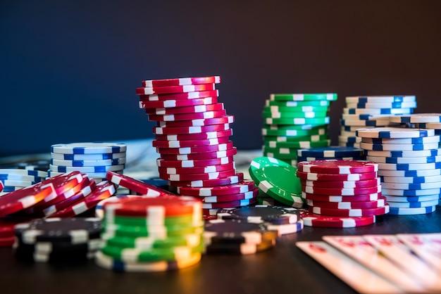 Żetony do pokera i karty do gry na czarnym stole.